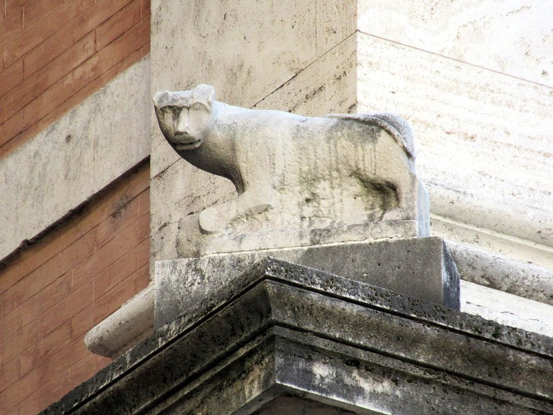 A stone cat from temple of Isis sits on a cornice of the Palazzo Grazioli, Rome